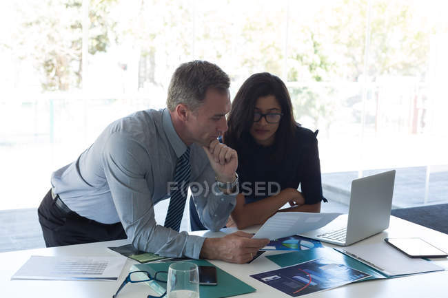 Business colleagues discussing over document in office — Stock Photo