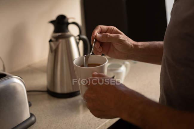 Mittleren Bereich der senior woman Küche zu Hause Kaffee einrühren — Stockfoto