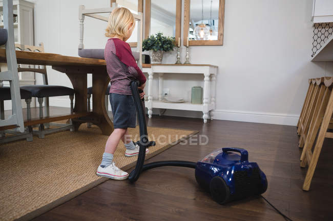 Boy using vacuum cleaner in living room at home — Stock Photo
