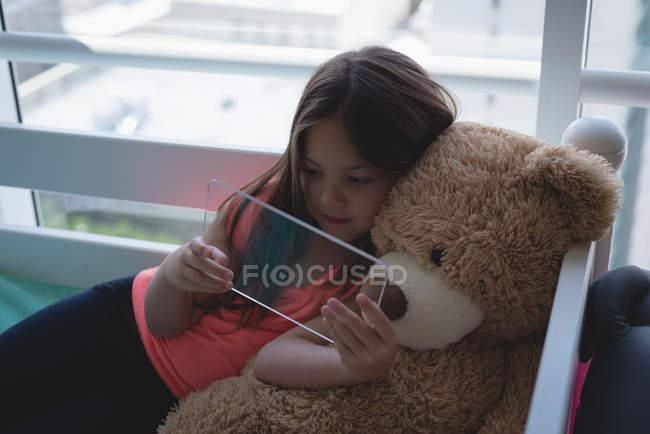 Niña con oso de peluche con tableta digital de vidrio en dormitorio - foto de stock