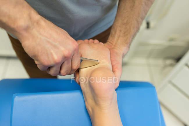 Massaggio gambe dando fisioterapista alla donna in clinica — Foto stock