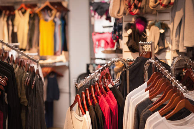 Сортів одяг висить на дисплеї на торговий центр — стокове фото