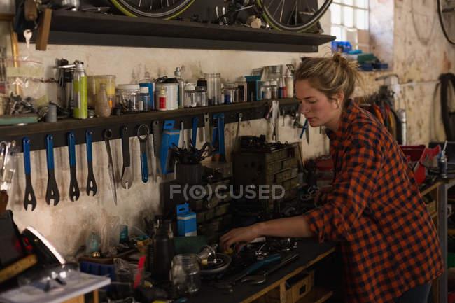 Female mechanic examining bicycle parts in workshop — Stock Photo