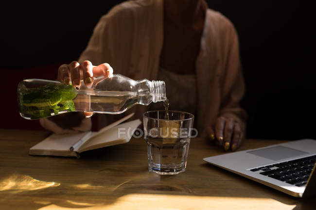 Mid section of woman pouring mint water into glass at cafe. — Stock Photo