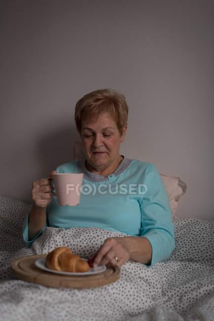 Donna anziana che prende caffè e colazione in camera da letto a casa — Foto stock