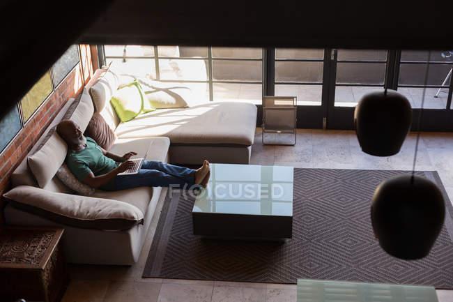 Пожилой мужчина использует ноутбук в гостиной дома — стоковое фото