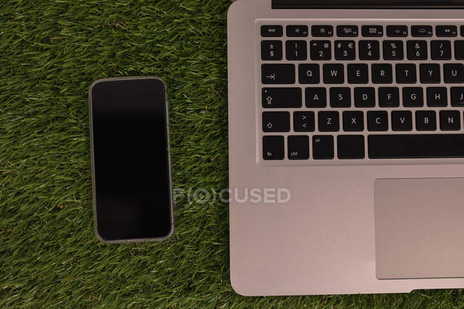 Close-up of laptop and mobile phone on artificial grass — Stock Photo
