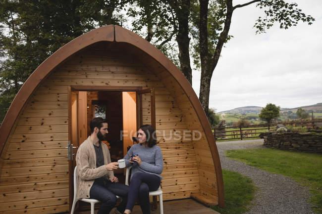 Пара, расслабляясь в бревенчатом домике на отдыхе — стоковое фото