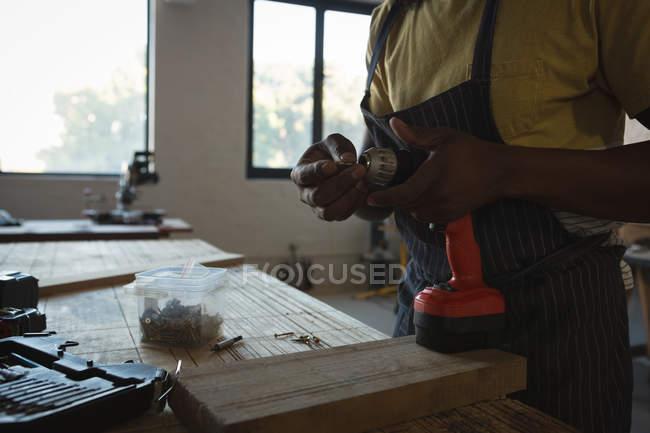 Mittelteil des Zimmermanns wechselt Nadel der Bohrmaschine in Werkstatt — Stockfoto