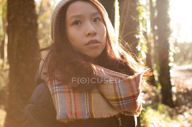 Thoughtful woman in warm clothing standing in forest — Stock Photo