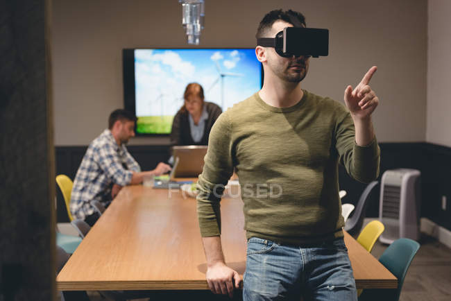 Businessman using virtual reality headset in meeting room at office — Stock Photo
