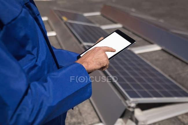 Розділ середині чоловічого працівник, використовуючи цифровий планшет на сонячної станції — стокове фото