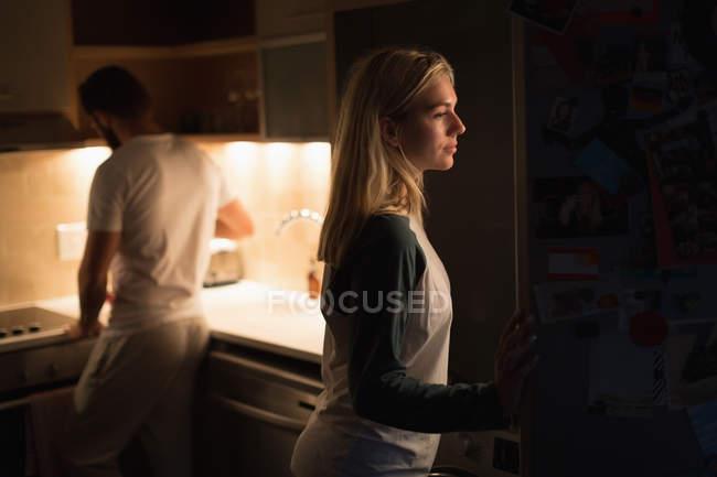 Frau, die Kühlschranktür zu öffnen, in der Küche zu Hause — Stockfoto