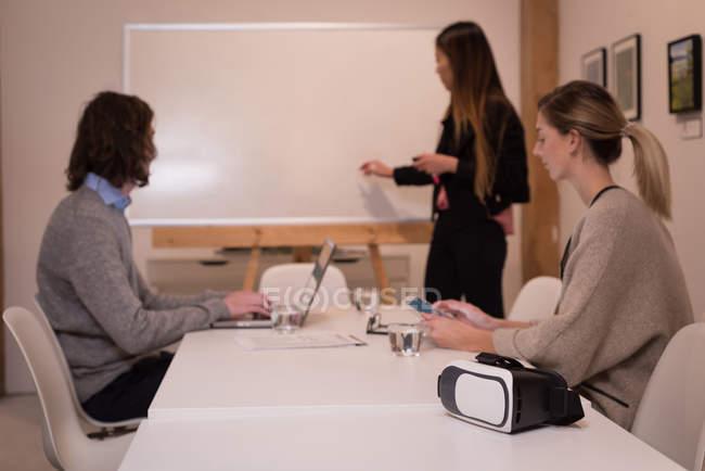 Colleghi d'affari che discutono sulla lavagna bianca in sala conferenze in ufficio . — Foto stock