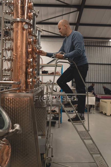 Male worker checking machine of distillery in factory — Stock Photo