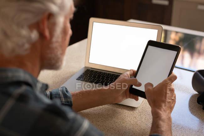 Старший мужчина с использованием цифрового планшета на кухне дома — стоковое фото