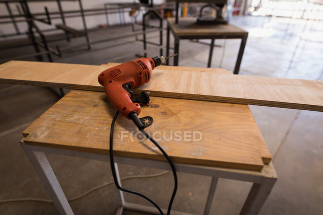 Bohrmaschine und Holzstück auf Tisch in Werkstatt. — Stockfoto