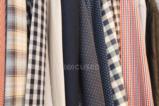 Nahaufnahme verschiedener Hemden, die zu Hause in Kleiderbügeln hängen — Stockfoto