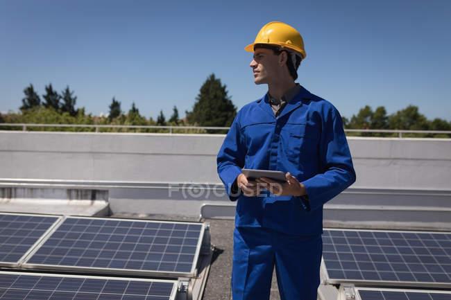 Travailleur masculin utilisant une tablette numérique à la station solaire par une journée ensoleillée — Photo de stock