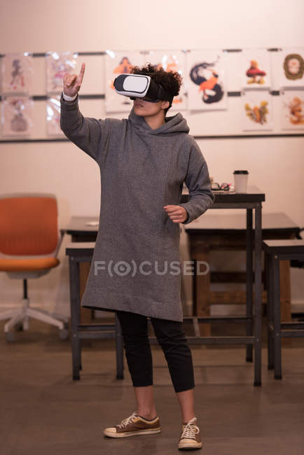 Молода жінка виконавчий за допомогою віртуальної реальності гарнітуру в офісі. — стокове фото