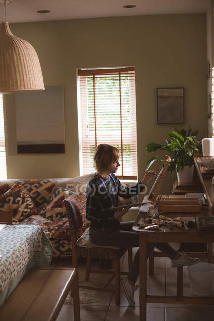 Female artist painting picture on canvas in living room at home — Stock Photo
