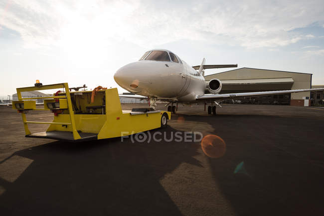 Private jet with trolley at terminal in sunlight — Stock Photo