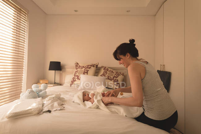 Smiling young mother changing baby diaper on bed in bedroom at home — Stock Photo