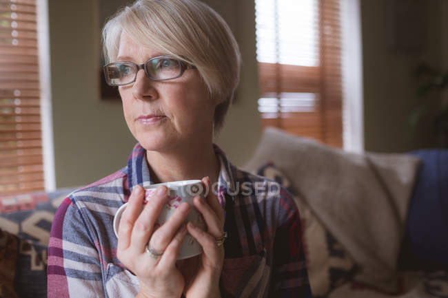 Thoughtful mature woman holding cup of coffee in living room at home — Stock Photo
