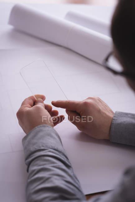 Général mâle à l'aide de téléphone portable de verre au bureau — Photo de stock