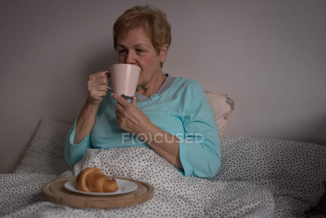 Senior woman having coffee and breakfast in bedroom at home — Stock Photo