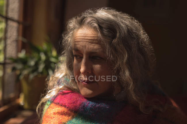 Close-up de mulher madura, embrulhada no cobertor, olhando pela janela — Fotografia de Stock