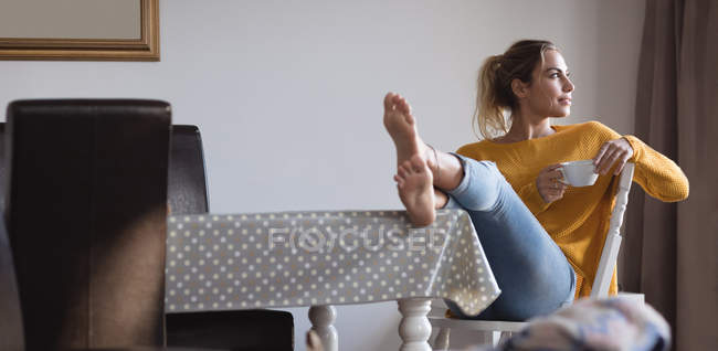 Thoughtful woman with feet up having coffee at home — Stock Photo