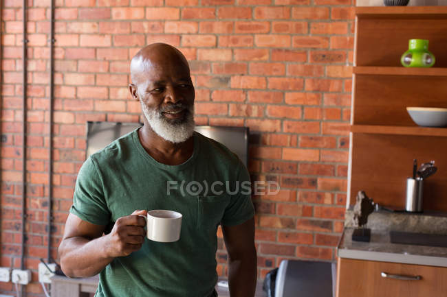 Smiling senior man having coffee at home — Stock Photo