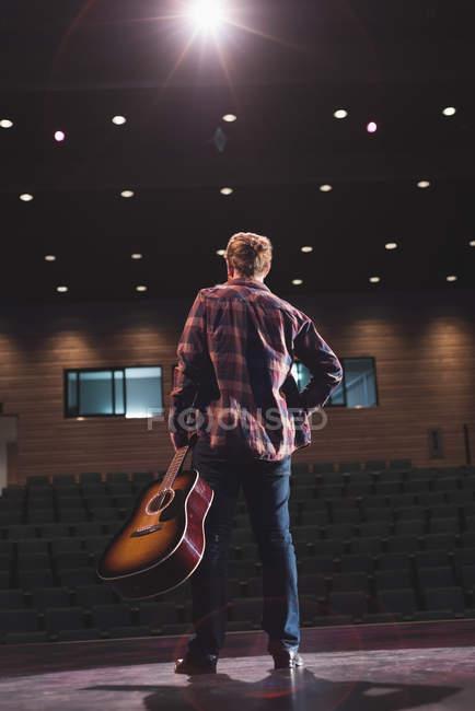 Человек с гитарой на сцену в театре. — стоковое фото