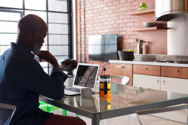 Thoughtful senior man using laptop at home — Stock Photo