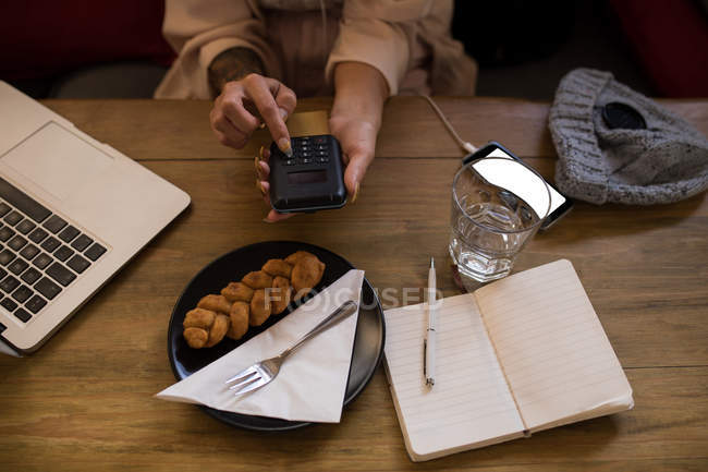 Mid section of woman using calculator in restaurant. — Stock Photo