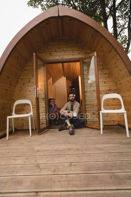 Вдумчивый пара, имея кофе на входе кабины журнала — стоковое фото