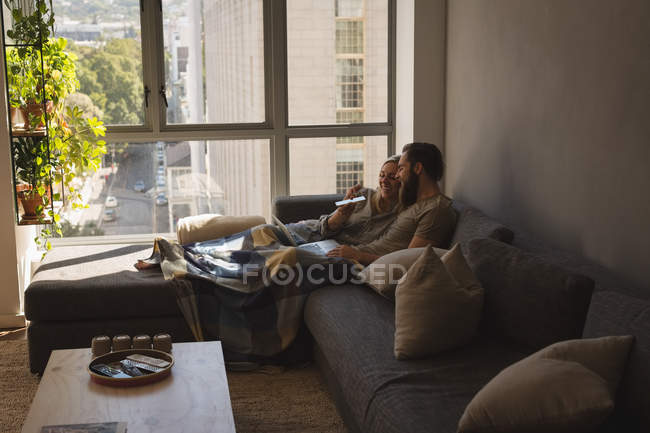 Couple using laptop and mobile phone in living room at home — Stock Photo
