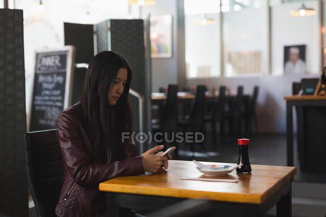 Молодая женщина, с помощью мобильного телефона в ресторане — стоковое фото