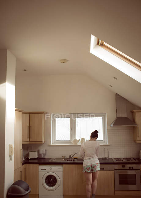 Rear view of woman working in kitchen interior at home. — Stock Photo