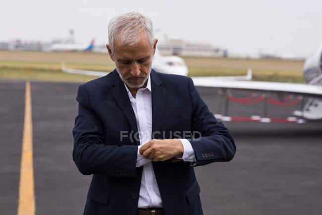 Старший бизнесмен, застегивал рукава рубашки на взлетно-посадочной полосы — стоковое фото