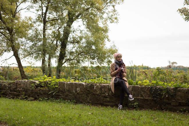 Nachdenkliche Frau in warmer Kleidung sitzt auf Steinmauer — Stockfoto