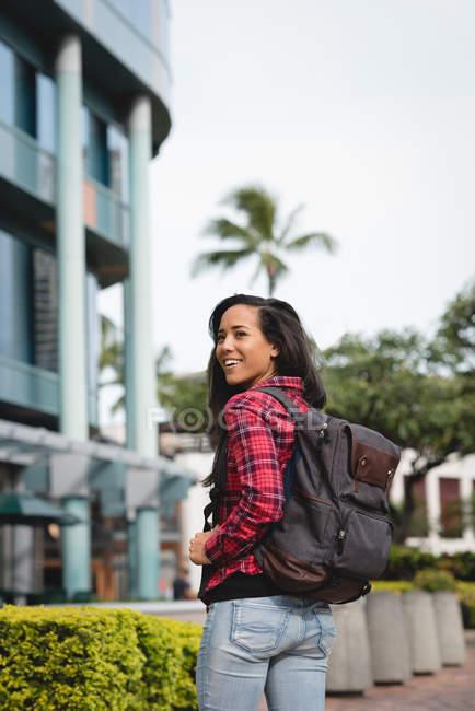 Улыбающиеся женщина с рюкзаком, стоя на улице и, глядя через плечо — стоковое фото