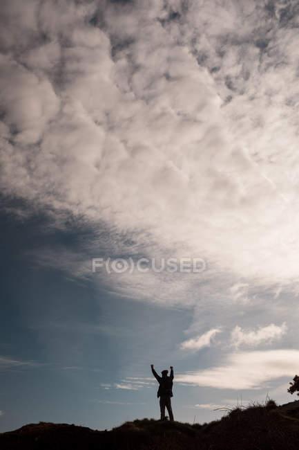 Silhouette eines männlichen Wanderers, der mit erhobenen Armen auf dem Land steht — Stockfoto