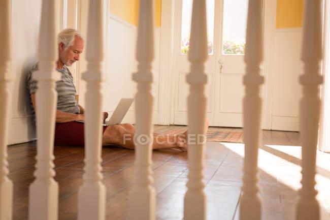 Aktiven senior Mann mit Laptop zu Hause — Stockfoto
