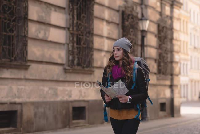 Junge Frau, die Karte zu betrachten, während des Gehens auf Straße — Stockfoto