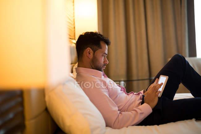Empresario usando tableta digital en habitación de hotel - foto de stock
