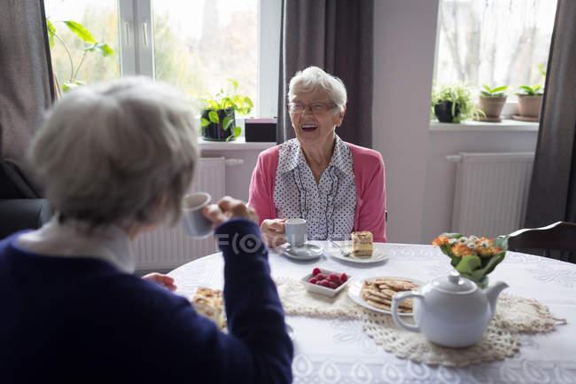 Senioren interagieren beim Kaffee zu Hause miteinander — Stockfoto