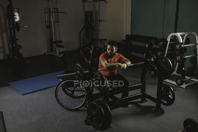 Handicapped man sitting and looking at barbell in gym — Stock Photo