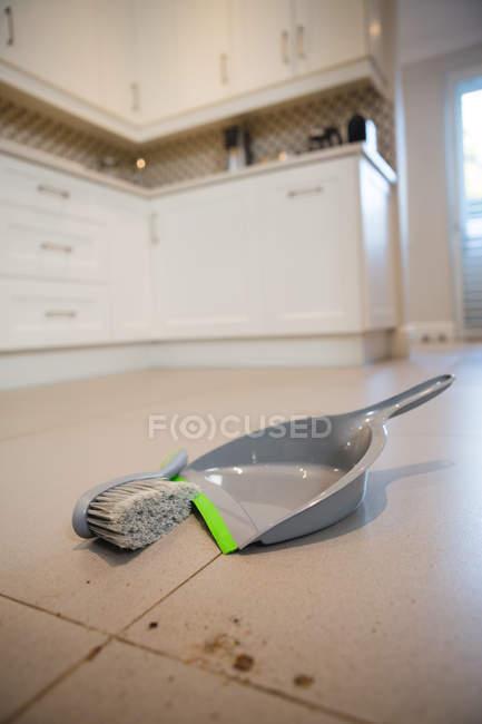 Крупный план пыли и щетки на полу дома — стоковое фото